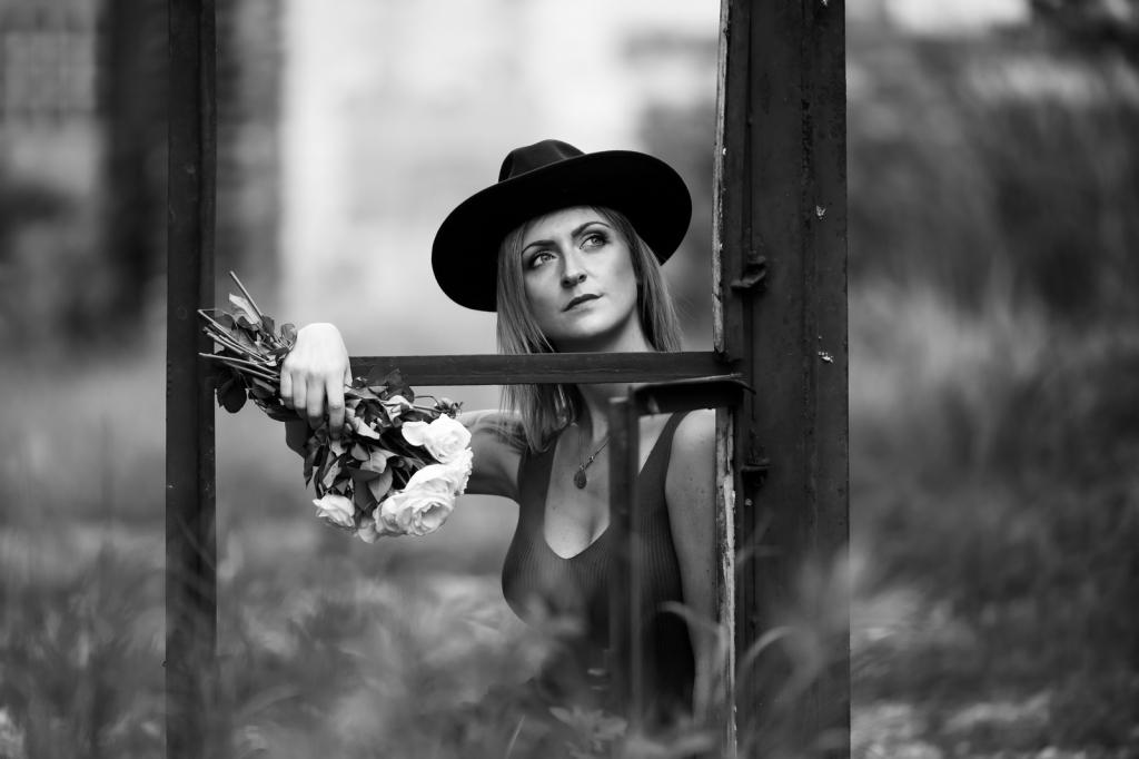 Frau, jung ,mit Hut am Fenster mit Blumen. Porträt,schwarzweiss