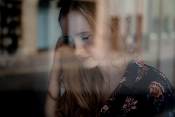 Porträt. Junge Frau verträumt , gespiegelt im Fenster.