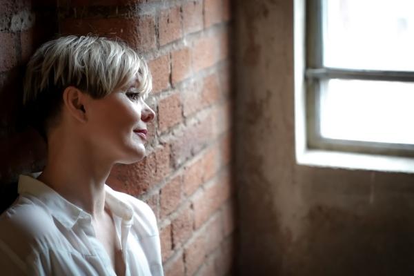 Porträt.Frau nachdenklich .Porträt an Backsteinwand und Fenster.